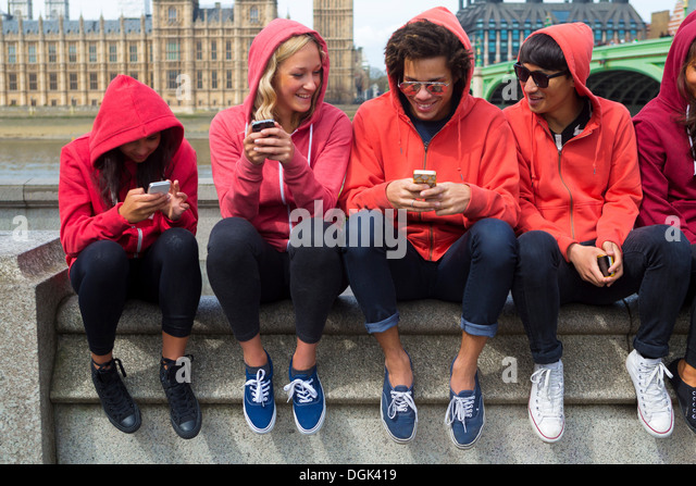 Group of young people looking at mobile phone - Stock Image