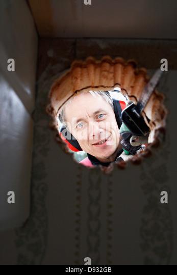 Smiling man sawing hole - Stock Image