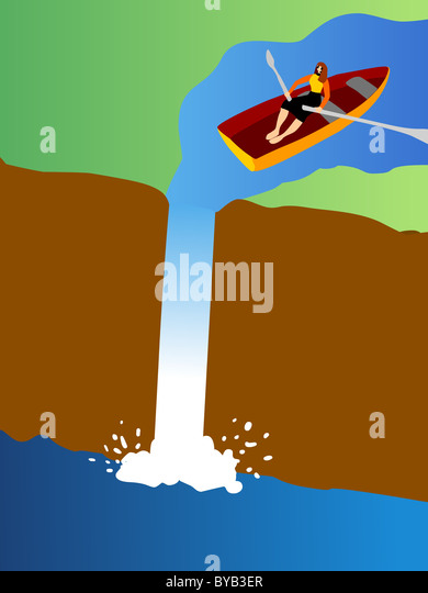 A small row boat going over a waterfall - Stock Image