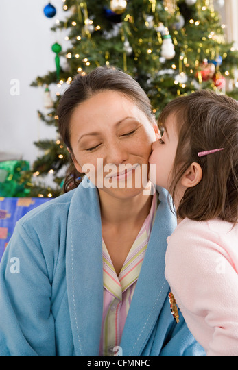 USA, California, Los Angeles, Girl kissing mother at Christmas morning - Stock Image