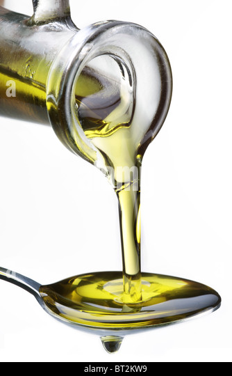 Olive oil flowing from carafe into the spoon isolated on a white. - Stock-Bilder
