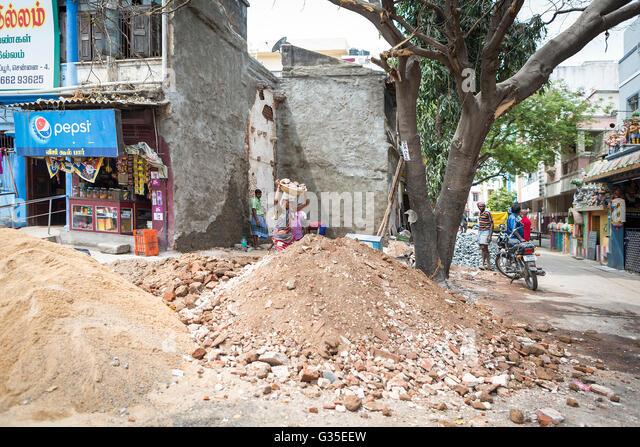 a-side-street-with-piles-of-rubble-on-th