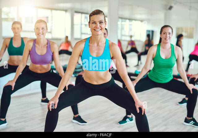 fitness, sport, training, people and lifestyle concept - group of women making squats in gym - Stock-Bilder