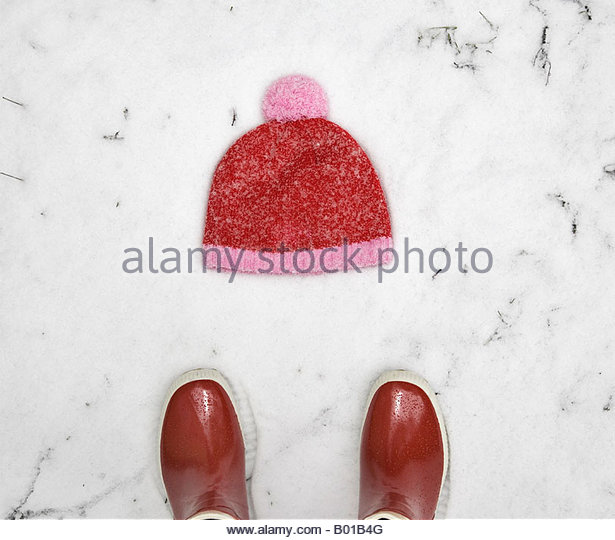 Close up of a pair of boots near a knit hat - Stock Image