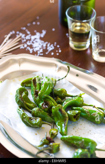 padron peppers as a typical Spanish tapas style snack on wood table , with sherry glasses and bottle in background - Stock Image