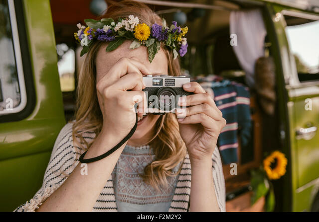 Hippie woman taking picture with analog camera in front of van - Stock Image