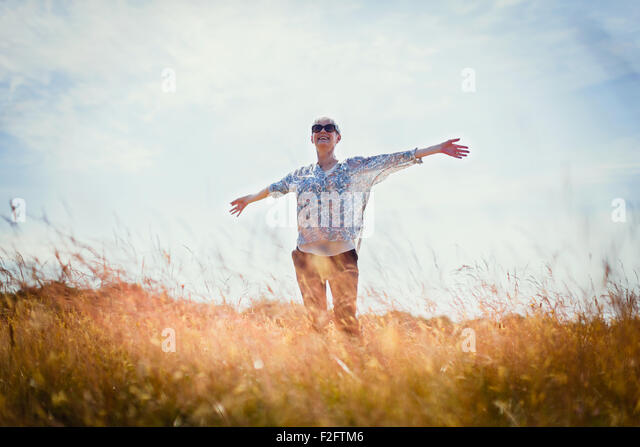 Carefree senior woman running with arms outstretched in sunny field - Stock Image