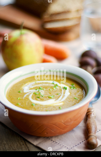 Carrot, Parsnip and Chestnut Bisque, garnished with soy yogurt and chives. - Stock Image