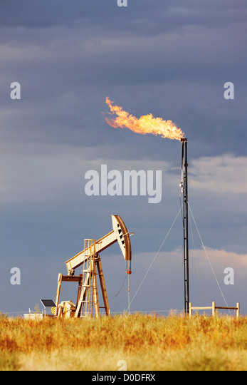 An oil well pump jack natural gas flare tower. pump jack is also known as pumpjack pumping unit grasshopper pump - Stock-Bilder