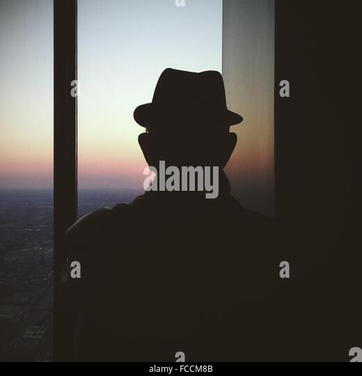 Rear View Of Silhouette Man Wearing Hat While Looking Through Window - Stock Image
