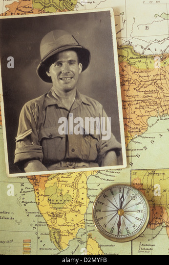 Black and white photograph of man in tropical military uniform placed with compass on map of India - Stock Image