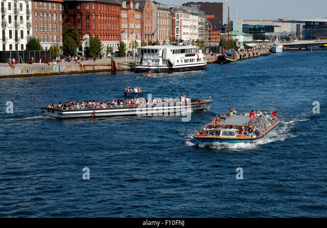 Crowded canal cruise boats on a busy summer's day at Havnegade in the port of Copenhagen - Stock Image