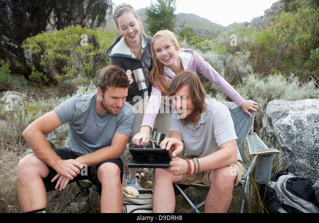 Group of young hikers looking at hand held computer during a break - Stock Image