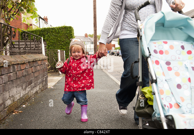 Toddler girl walking with mother - Stock-Bilder