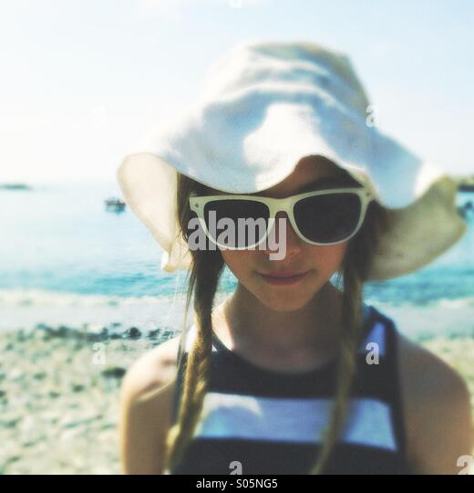 Girl teen  in floppy whit hat and sunglasses on the beach - Stock Image