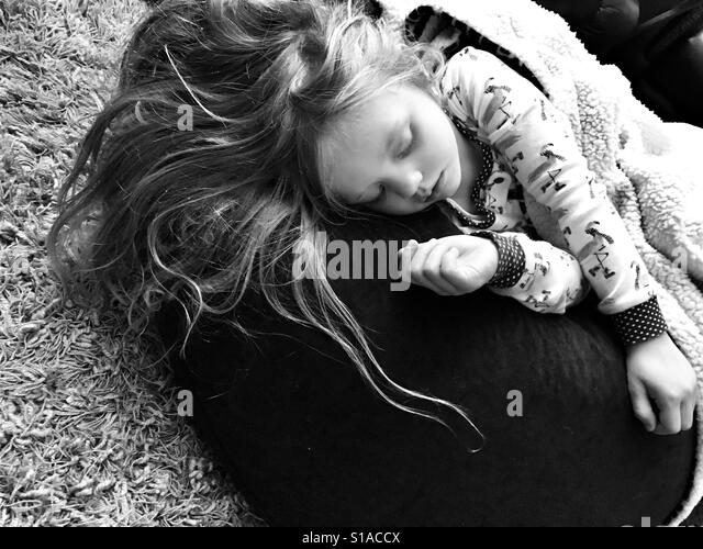 Little girl sleeping on a bean bag - Stock-Bilder