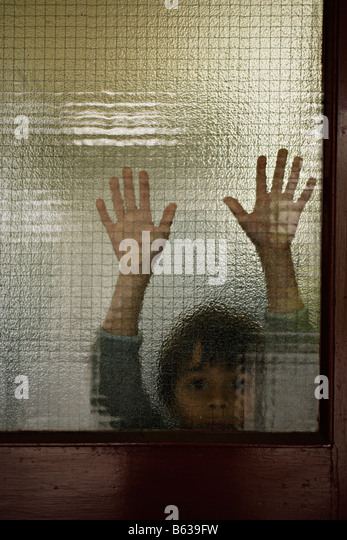 Six year old boy behind glass - Stock-Bilder