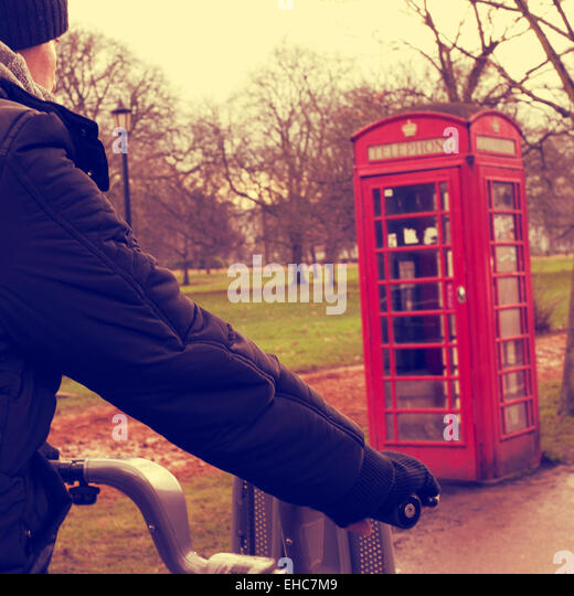 a young man riding a bicycle in Hyde Park in winter in London, United Kingdom, with a typical red telephone booth - Stock Image