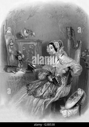 An artistic young woman sits  with a book in her hand  surrounded by evidence of her  other creative hobbies  including - Stock-Bilder