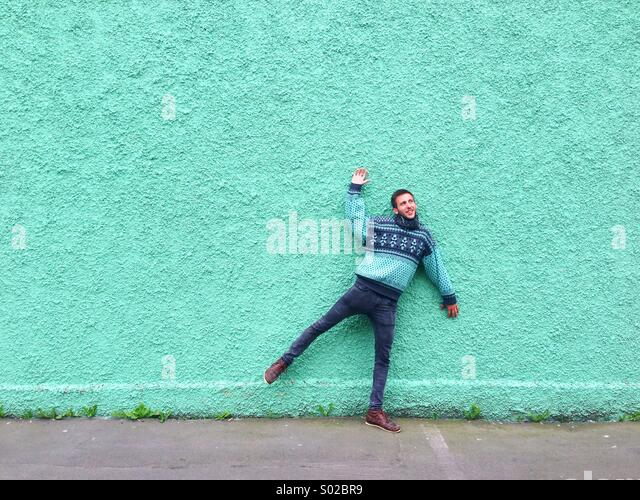 Man simulating that he's been stuck on a green wall - Stock Image