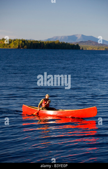 A man paddles his canoe on Seboeis Lake near Millinocket, Maine.  Mount Katahdin is in the distance. (MR) - Stock Image