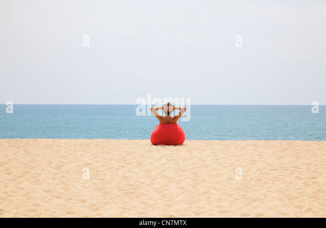 Man relaxing in beanbag on beach - Stock Image