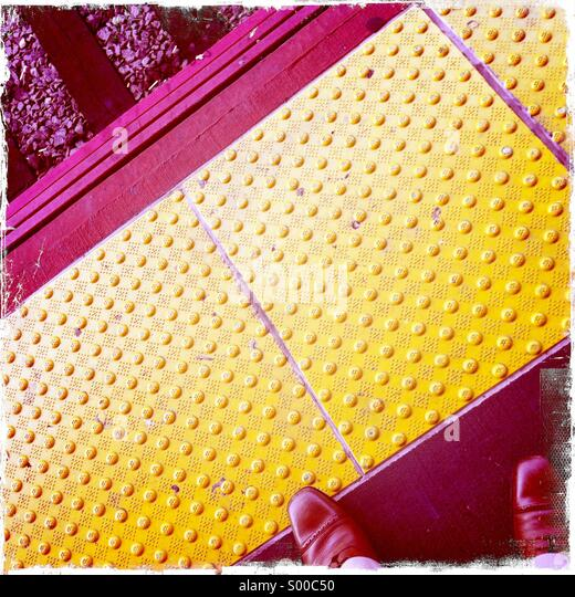 Railway station platform with commuter waiting patiently. - Stock Image