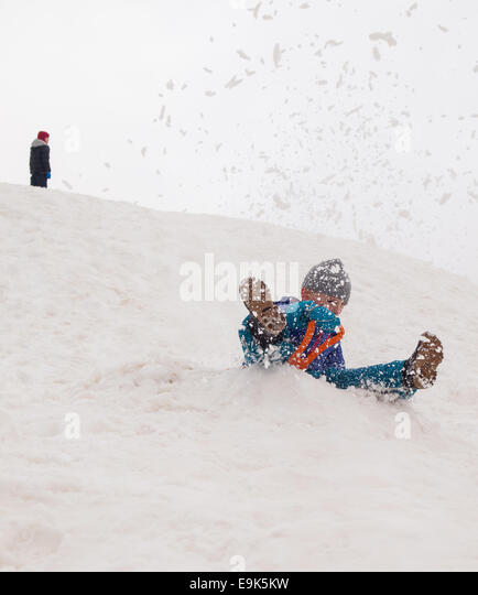 small boy sledging fast down a steep hill in a cloud of snow with child standing at top of hill in background - Stock Image