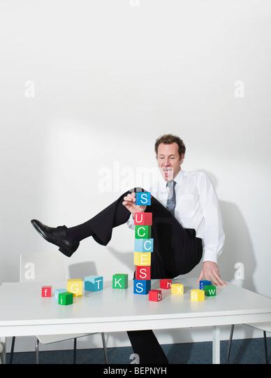 Business man puts last block on tower - Stock Image