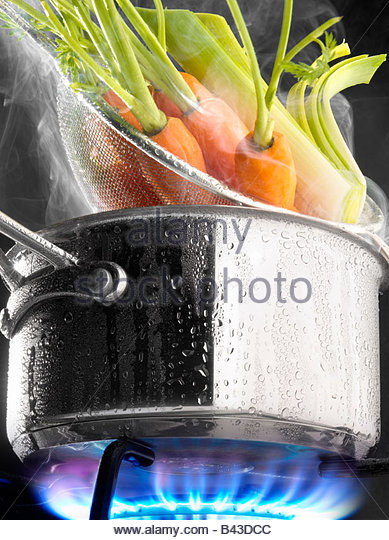 Steam cooking carrots in a saucepan on a gas cooker - Stock Image
