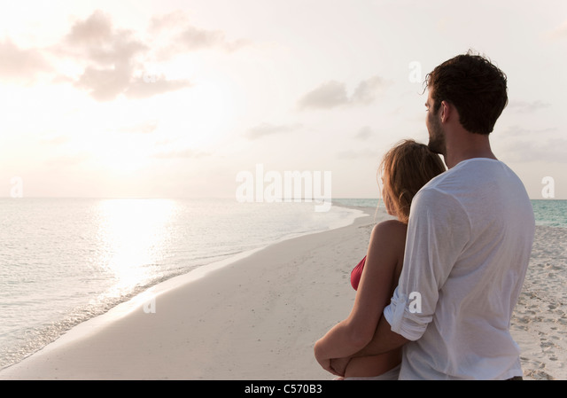Couple admiring horizon at beach - Stock Image
