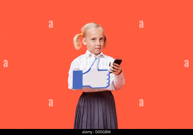 Portrait of a young schoolgirl with cell phone holding fake like button over orange background - Stock Image