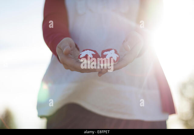 Pregnant woman holding small baby shoes - Stock Image