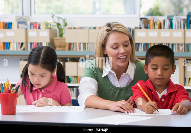 Two students in class writing with teacher helping - Stock Image