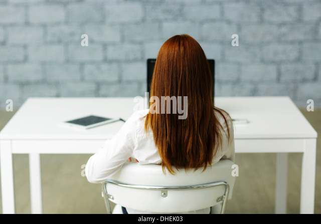 Picture from behind of a businesswoman sitting at her desk - Stock Image