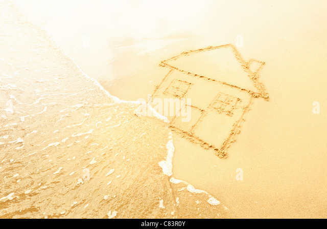 House in sand washed away by waves - Stock Image