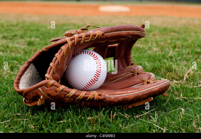 Baseball and glove on field with base and outfield in background. - Stock Image