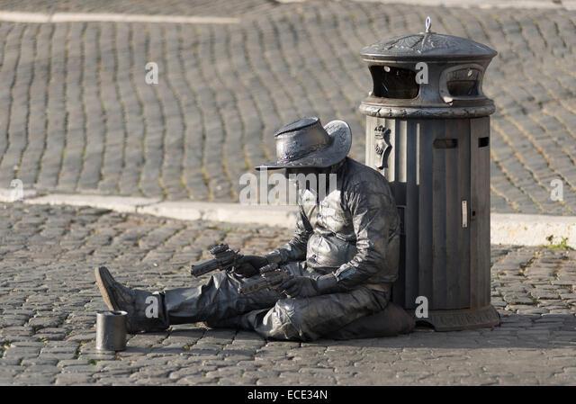 Cowboy, actor with guns sitting on the Via della Conciliazone, XIV rione Borgo, Rome, Lazio, Italy - Stock Image