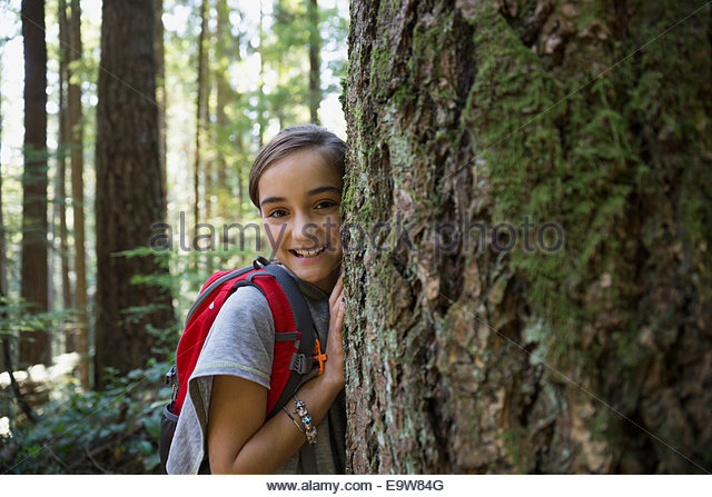 Portrait of smiling girl hugging tree trunk - Stock Image