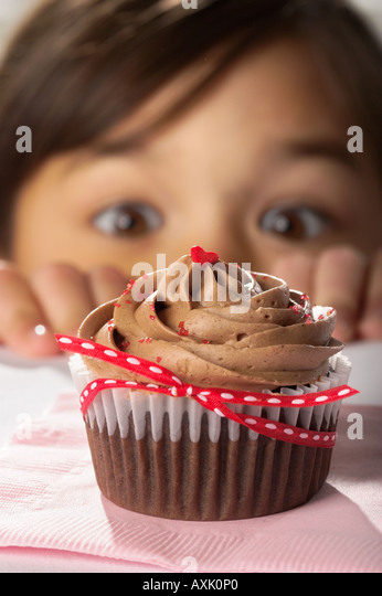 child boy eyes cupcake sweet tasty desert decorations holiday Valentines heart love person brown hands want desire - Stock Image
