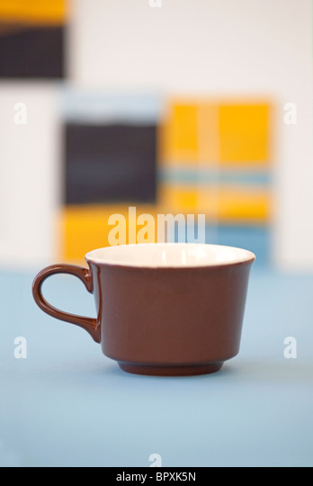 brown coffee cup in artists studio with paintings in background - Stock Image