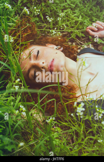 Young redhead woman enjoying nature - Stock Image