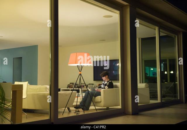 Man using laptop in living room, viewed through window - Stock-Bilder