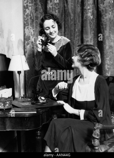 1930s TWO SMILING WELL DRESSED WOMEN ONE SITTING ONE STANDING BY VANITY TABLE TALKING ON TELEPHONE - Stock Image