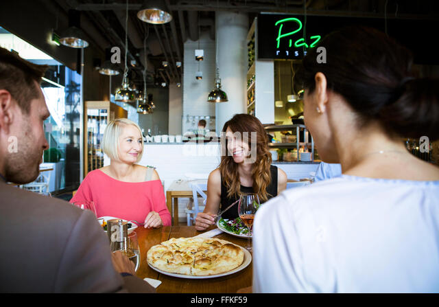 Group of friends celebrating in restaurant - Stock Image