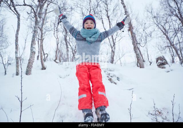 Boy jumping down snow covered hill, Hemavan,Sweden - Stock Image