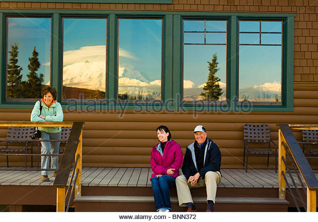 Guests watching the sunset on Mt. McKinley from porch of Potlatch Dining Room at Camp Denali in Denali National - Stock Image