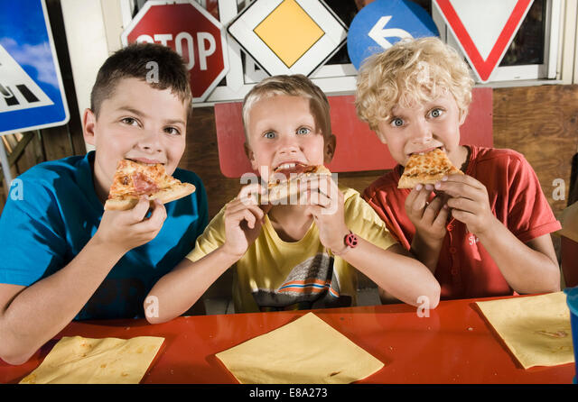 Three boys eating pizza at driver training area - Stock Image