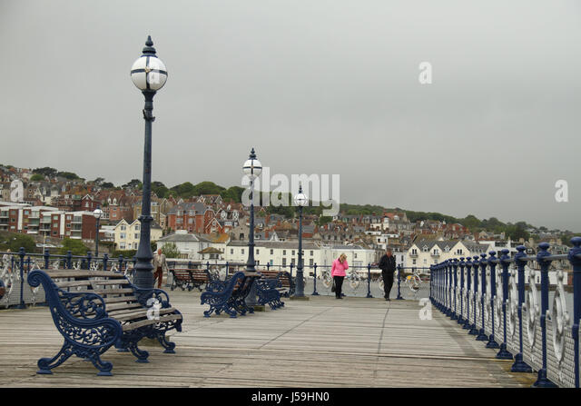 Swanage, UK -  12 May: Public benches on the Swanage pier. General view of the seaside town of Swanage in Dorset, - Stock Image