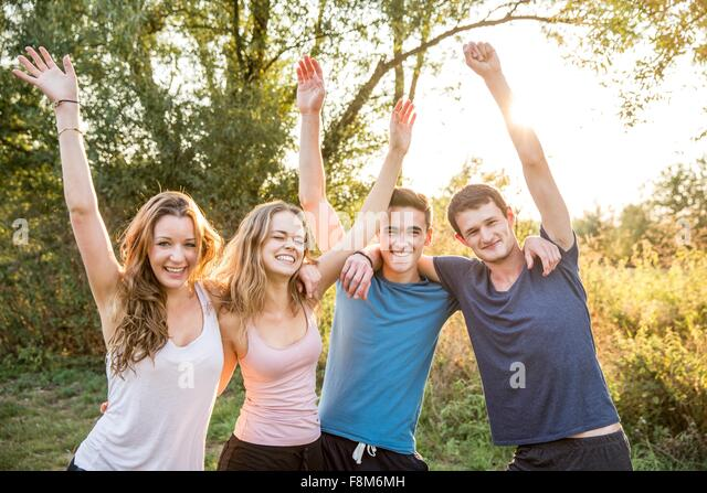 Portrait of group of friends in rural environment, arms raised, smiling - Stock Image